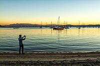 Homem fotografando a paisagem na Praia de Santo Antonio de Lisboa ao por do sol. Florianópolis, Santa Catarina, Brasil. / Man photographing the landscape in Santo Antonio de Lisboa Beach at sunset. Florianopolis, Santa Catarina, Brazil.