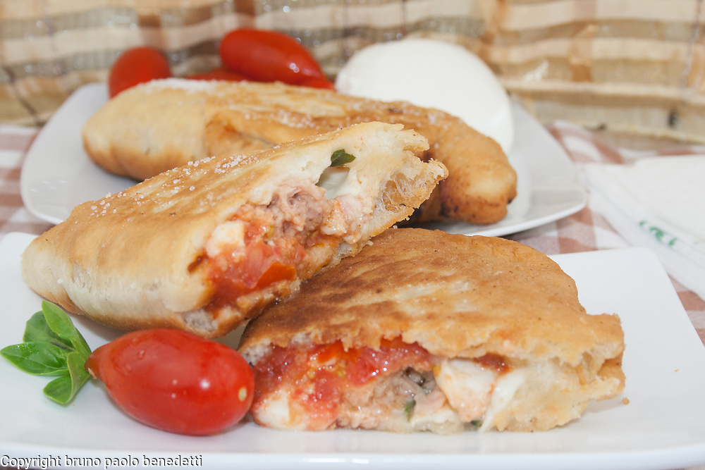 panzerotti or fried pizza with canned tuna fish and mozzarella filling side-view cloe-up from above on white dish whole and section,italian traditional food of Apulia