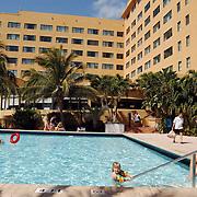 Vakantie Miami Amerika, hotel, zwembad, toeristen, zwemband, zwemmen, palmbomen, palmboom, kind, ouder, moeder, zon, zonnen