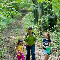 A woman and two girls walk a forest trail at the Pell Farm in Grafton, Massachusetts.