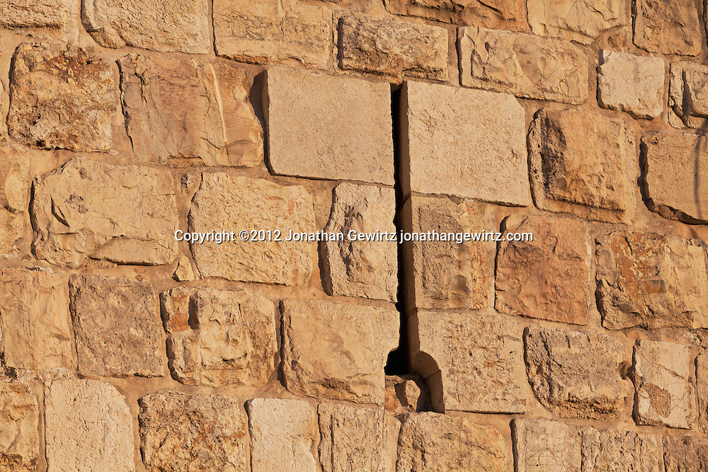 An arrowslit in the stone exterior wall of the Old City of Jerusalem.