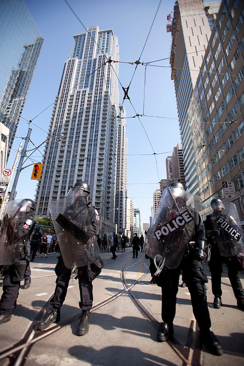 Police in riot gear look on as protestors march through the streets of Toronto, Canada, June 25, 2010 as the G8 leaders gather for their summit in Huntsville, Ontario. The G20 moves to Toronto on Saturday.<br /> AFP/GEOFF ROBINS/STR