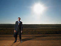 Isolated businessman standing in deserted road