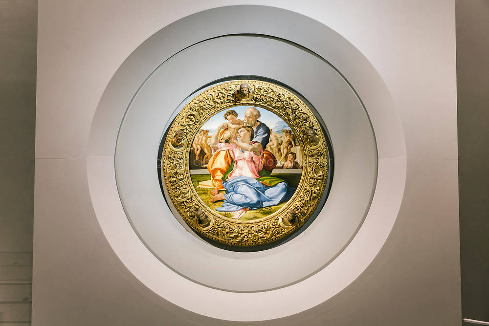 FLORENCE, ITALY - 3 JUNE 2018: The &ldquo;Holy Family&rdquo;, also known as the Doni Tondo, that Michelangelo painted for the Doni couple around 1503-1504, is seen here in its new location in room 41at the Uffizi, in Florence, Italy, on June 3rd 2018.<br /> <br /> As of Monday June 4th 2018, Room 41 or the &ldquo;Raphael and Michelangelo room&rdquo; of the Uffizi is part of the rearrangement of the museum's collection that has<br /> been defining Uffizi Director Eike Schmidt&rsquo;s grander vision for the Florentine museum.<br /> Next month, the museum&rsquo;s Leonardo three paintings will be installed in a<br /> nearby room. Together, these artists capture &ldquo;a magic moment in the<br /> first decade of the 16th century when Florence was the cultural and<br /> artistic center of the world,&rdquo; Mr. Schmidt said. Room 41 hosts, among other paintings, the dual portraits of Agnolo Doni and his wife Maddalena Strozzi painted by Raphael round 1504-1505, and the &ldquo;Holy Family&rdquo;, that Michelangelo painted for the Doni couple a year later, known as the<br /> Doni Tondo.