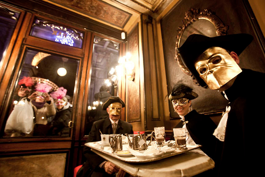 """Masked revellers have a coffee break at """"Florian Café"""" in Saint Mark Square during the first day of Venetian Carnival in Venice."""