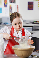 Girl (10-12) with Down syndrome sieving flour into bowl