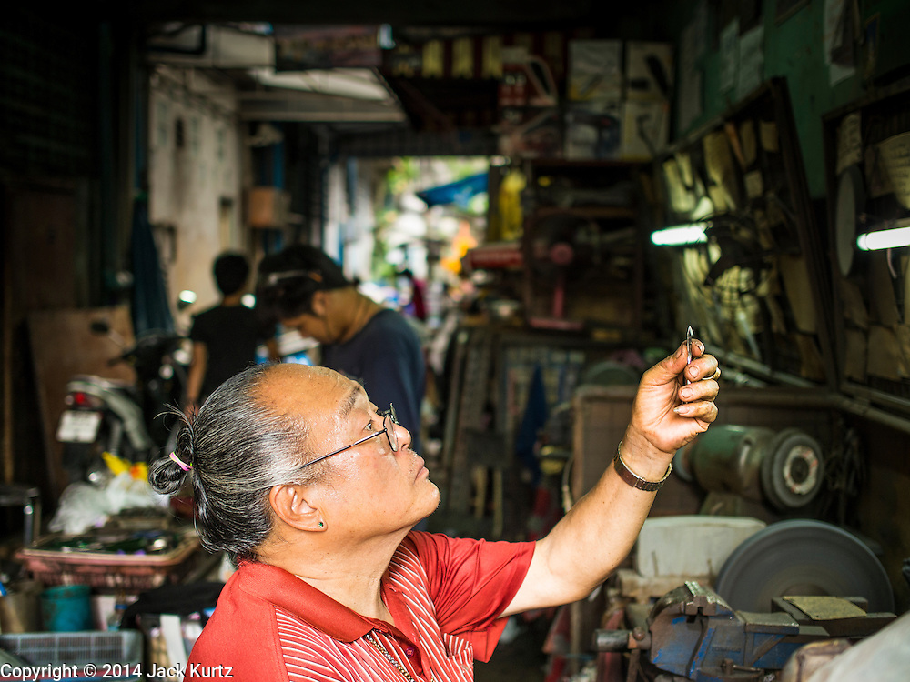 29 APRIL 2014 - BANGKOK, THAILAND: A tool maker works on a pair of cuticle clippers in his street stall in the Thonburi section of Bangkok.     PHOTO BY JACK KURTZ