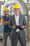 Portrait of smiling young male manager holding clipboard with worker in background at industry
