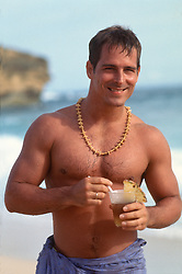 Shirtless man at the beach holding a tropical cocktail