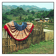 Hand embroidered Hmong dress draped over a bamboo fence amidst the vast green landscape of Bac Ha in Northern Vietnam, Southeast Asia