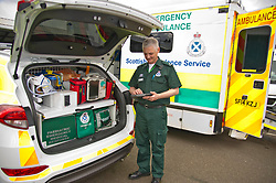 Pictured: Ian Stark checks the new tablet fitted to vehicles in Scottsih Ambulance Service<br /> <br /> Health Secretary Shona Robison met paramedics today on a visit to Scottish Ambulance Service's city station where she announced new funding for the service<br /> Ger Harley | EEm 24 April 2017