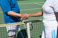 Two people shaking hands over tennis net