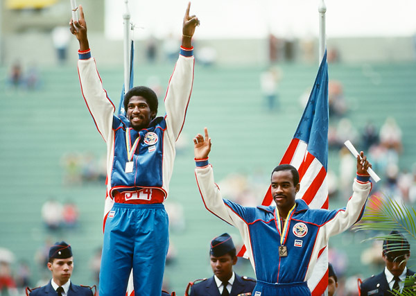 CARACAS, VENEZUELA -  AUGUST 1983:  Roger Kingdom (left) and Tonie Campbell (right) of the USA wave to the crowd during the medal ceremony for the Men's 110 meter hurdles event of the track and field competition of the 1983 Pan Am Games held in August 1983 in Caracas, Venezuela.  Kingdom was the gold medalist and Campbell the bronze medalist in the event.  (Photo by David Madison/Getty Images) *** Local Caption *** Roger Kingdom;Tonie Campbell