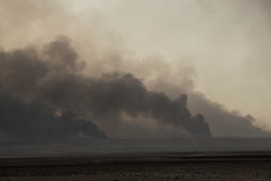 Licensed to London News Pictures. 02/11/2016. Qayyarah, Iraq. Plumes of smoke, visible for many miles, rise from the Qayyarah Oilfields south of Mosul, Iraq.<br /> <br /> Two months after being liberated from the Islamic State, the Iraqi town of Qayyarah, located around 30km south of Mosul, is still dealing with the environmental repercussions of their ISIS occupation. The town's estimated 15,000 inhabitants constantly live under, and in, heavy clouds of smoke which often envelope the settlement. The clouds emanate from burning oil wells in a nearby oil field that were set alight by retreating ISIS extremists after a two year occupation. The proximity of the fires, often right next to homes within the town, covers many buildings and residents with thick soot and will lead to long term health and environmental implications. Photo credit: Matt Cetti-Roberts/LNP
