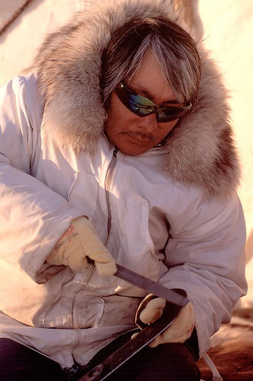 Alaska Native whaler at camp on the sea ice, sharpening a traditional knife