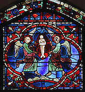 Once his body arrives in Constantinople, the soul of St Stephen rises to heaven in the form of a small naked body in a mandorla, accompanied by 2 angels. Section of the elevation of the soul, 1220-25, from the Life of St Stephen and transferral of his relics window in the ambulatory of Chartres Cathedral, Eure-et-Loir, France. This window, unusually dominantly red in colour, tells the story of the life of St Stephen, the first Christian martyr, who died c. 36 AD and whose relics are held at Chartres. It is situated in the chapel dedicated to martyrs. Chartres cathedral was built 1194-1250 and is a fine example of Gothic architecture. Most of its windows date from 1205-40 although a few earlier 12th century examples are also intact. It was declared a UNESCO World Heritage Site in 1979. Picture by Manuel Cohen