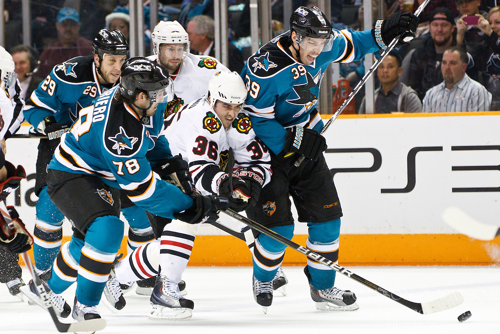 December 11, 2010; San Jose, CA, USA; Chicago Blackhawks center Dave Bolland (36) is checked by San Jose Sharks center Benn Ferriero (78) and center Logan Couture (39) during the second period at HP Pavilion. Mandatory Credit: Jason O. Watson / US PRESSWIRE