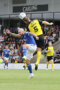 Burton Albion defender Jake Buxton heads the ball clear from Ipswich Town midfielder James Norwood during the EFL Sky Bet League 1 match between Burton Albion and Ipswich Town at the Pirelli Stadium, Burton upon Trent, England on 3 August 2019.