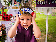 25 APRIL 2012 - PHOENIX, AZ: HERMAN RUBIO, 3, from Phoenix, adjusts his head band with an American flag on it, before an immigrants' prayer vigil at the Arizona capitol Wednesday. Herman and his family were there to show their opposition to SB1070. Immigrants' rights groups opposed to SB1070 and Tea Party affiliated groups that support SB1070 gathered at the state capitol in Phoenix Wednesday to express their opposition and support of the bill. SB1070 was signed by Arizona Governor Jan Brewer in April 2010. At the time it was the toughest anti-illegal immigration bill in the country. Immigrants' rights groups sued Arizona and the federal courts stopped enforcement of the bill. The bill ended up in the US Supreme Court which heard arguments Wednesday. A ruling on the bill is expected in June.    PHOTO BY JACK KURTZ