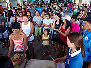 21 JANUARY 2018 - CAMALIG, ALBAY, PHILIPPINES: People line up for relief supplies at the Barangay Cabangan evacuee shelter in a school in Camalig. There are about 650 people living at the shelter. They won't be allowed to move back to their homes until officials determine that Mayon volcano is safe and not likely to erupt, which could take at least two more weeks. More than 30,000 people have been evacuated from communities on the near the Mayon volcano in Albay province in the Philippines. Most of the evacuees are staying at schools in communities outside of the evacuation zone.   PHOTO BY JACK KURTZ