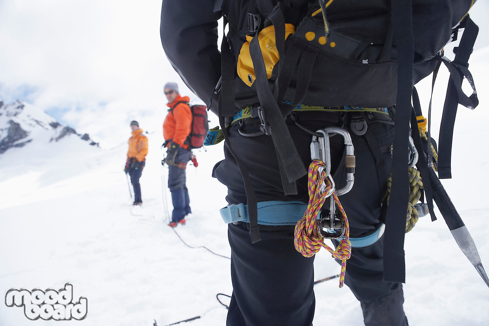 Hiker's back with backpack and safety rope in snowy mountains with two friends ahead back view