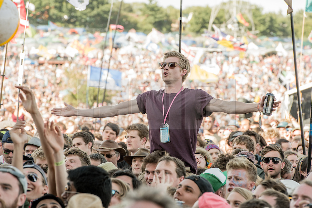 © Licensed to London News Pictures. 28/06/2015. Pilton, UK.Festival goers watch Alt J perform on the Pyramid Stage at Glastonbury Festival 2015 on Sunday Day 5 of the festival.  This years headline acts include Kanye West, The Who and Florence and the Machine, the latter being upgraded in the bill to replace original headline act Foo Fighters.  Photo credit: Richard Isaac/LNP