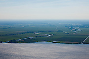 Nederland, Utrecht, Gemeente Eemnes, 06-09-2010; polders tussen Eemnes en Spakenburg gezien vanuit Flevoland. Een van de laatste open polderlandschappen in de Randstad, aan de horizon het Gooi, het riviertje de Eem mondt uit in het Eemmeer.  De polders zijn: Zuidpolder te Veld, Noordpolder te Veld, Maatpolder Bikkerspolder. .Polders between Eemnes and Spakenburg seen to Flevoland. One of the last open polder landscapes in the Randstad. The river Eem flows into the Eemmeer..luchtfoto (toeslag), aerial photo (additional fee required).foto/photo Siebe Swart