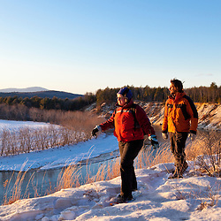 A man and woman snowshoeing on a bluff overlooking the Merrimack River in Canterbury, New Hampshire.