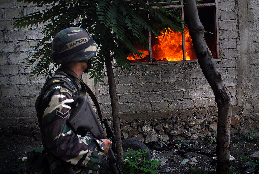 Malaysian troops search house to house, after rumours of a gunman brought them to the Comora area of Dili. Later, gangs burn nearby buildings. 04/06/06