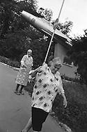 Two women joking in a Bishkek street beneath the nose of a Soviet era fighter plane,  Kyrgyzstan.