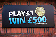 An advert for Dunes Amusements offering play a game for £1 and win £500.