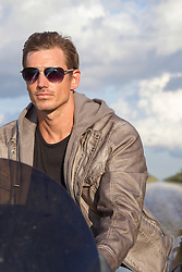 handsome man with sunglasses driving a motorboat in The Everglades