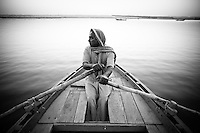 Man rows his boat across the calm ganges river