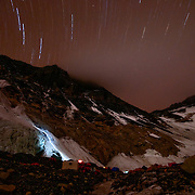 Headlamps of Sherpa climbers streak up the Southwest Face of Mount Everest at night. The Sherpa climbers were working as park of the 2009 Korean Southwest Face Expedition; thanks to the hard work and dedication of the Sherpa, the Korean team established a new route on the Southwest Face and put four clibmers on the summit.