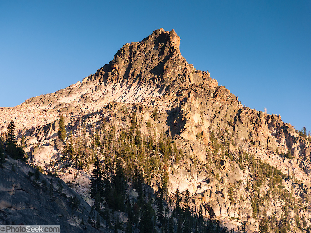 A granite peak rises in the Sawtooth Wilderness (above Redfish Lake Creek), Blaine County, Idaho, USA. The Sawtooth Range (part of the Rocky Mountains) are comprised of the pink granite of the 50 million year old Sawtooth batholith. Sawtooth Wilderness, managed by the US Forest Service within Sawtooth National Recreation Area, has some of the best air quality in the lower 48 states (says the US EPA).