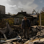 A local man inspects an unexploded missile lodged among the rubble of his garden shed in a neighbourhood close to Donetsk airport.