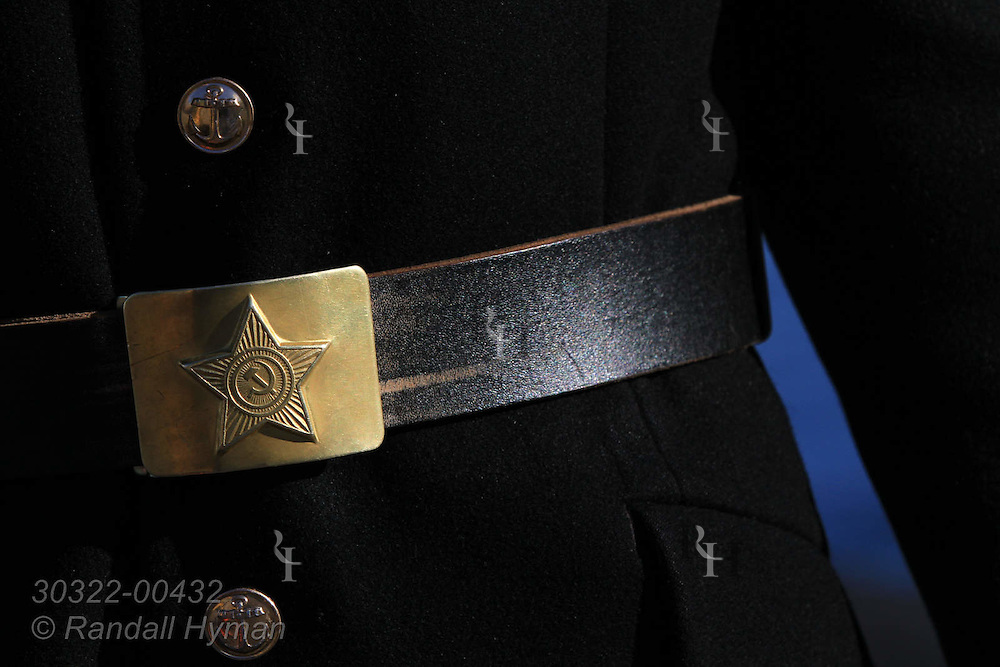 Soviet hammer and sickle inside star adorn Russian military belt buckle on guide's uniform at Pyramiden, the once-flourishing Soviet-era coal mining town abandoned in 1998 at Isfjorden on Spitsbergen island, Svalbard, Norway.