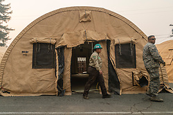 November 16, 2018 - California, U.S. - Sgt. MANGHIRMALANI, a member of California Air National Guard 129th Rescue Wing, right, and ENAFAYE NINE-ROWE, a member of Chico California Conservation Corp Crew 28, walk past an isolation tent at East Ave Church in Chico. Many of the evacuees from the Camp Fire are being given shelter in nearby Chico. (Credit Image: © Daniel Kim/Sacramento Bee via ZUMA Wire)