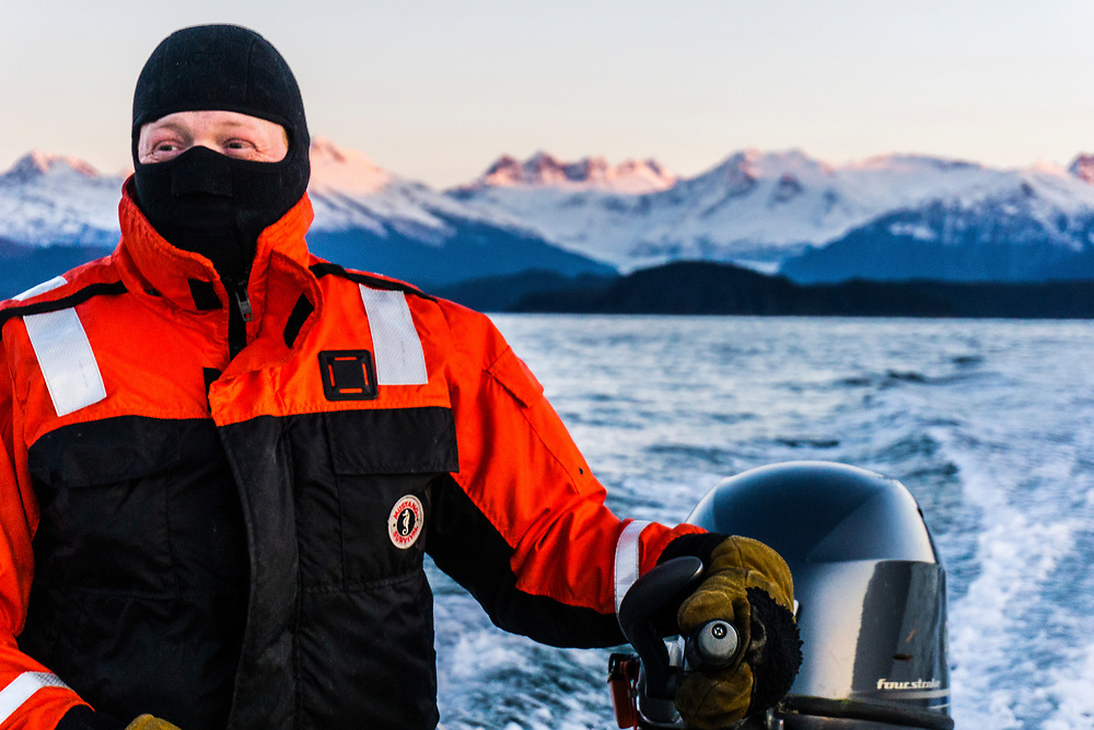 Nathan Adams operates his skiff in Auke Bay, outside Juneau, Alaska. The Mendenhall Glacier and Mendenhall Towers are visible behind. MR, MRA