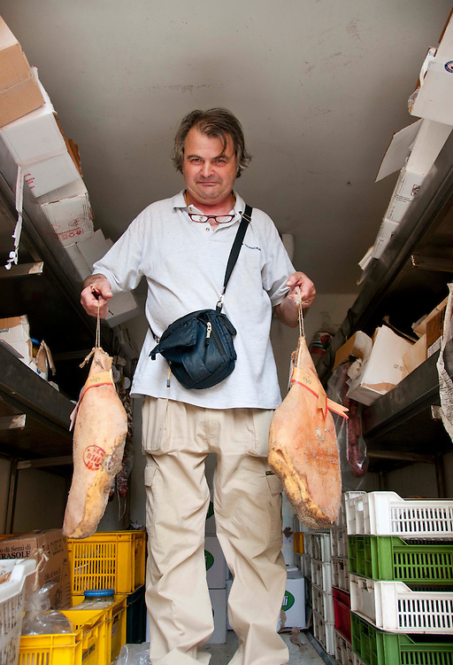 In Siena, the Tuscany region of Italy, natives make their living selling meat to local butcher shops. Pietro Bacciottini is a distributor and makes daily rounds delivering various meats in the area. He holds two pieces of salted pork while standing in the back of his van.
