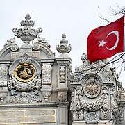 A Turkish flag flies in front of the main gate at Dolmabahçe Palace. Dolmabahçe Palace, on the banks of the Bosphorus Strait, was the administrative center of the Ottoman Empire from 1856 to 1887 and 1909 to 1922. Built and decorated in the Ottoman Baroque style, it stretches along a section of the European coast of the Bosphorus Strait in central Istanbul.
