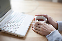 Hand holds a cup of black tea and laptop keyboard