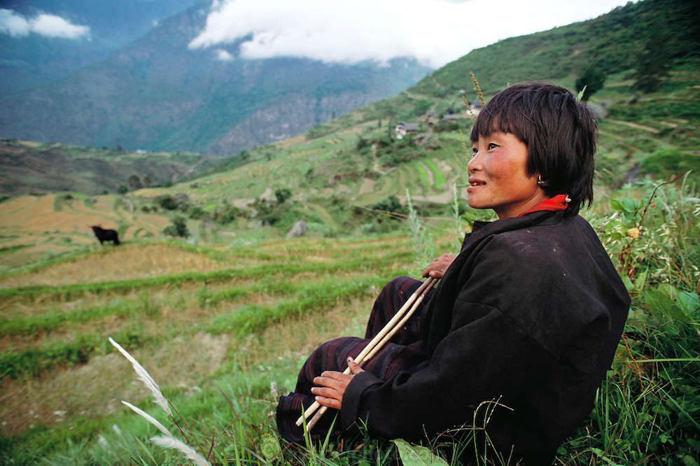 Sangay sits in the terraced rice and wheat fields near her village of Shingkhey, Bhutan. She and her mother Nalim take turns caring for the younger children at home and working on planting and harvesting their crops. The family farms both land that they own and land that they rent. It is scattered in terraced strips through the hillsides near their home, each plot devoted to one crop: wheat, rice, chilies, or potatoes. Shingkhey, Bhutan. From Peter Menzel's Material World Project that showed 30 statistically average families in 30 countries with all their possessions.