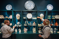 © Licensed to London News Pictures. 25/06/2019. LONDON, UK. Staff members make adjustments to their stand of historic ceramic pieces at E & H Manners gallery at a preview of Masterpiece London 2019, the world's leading cross-collecting art fair held in the grounds of the Royal Hospital Chelsea.  The fair brings together 157 international exhibitors presenting works from antiquity to the present day and runs 27 June to 3 July 2019.  Photo credit: Stephen Chung/LNP