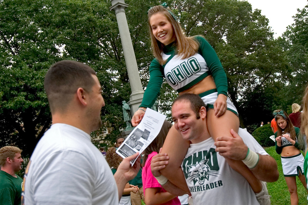 "Ohio University cheerleaders Amy McLaren and Chris Groman greet members of the 2006 freshman class as they enter the activities fair on the College Green...OPENING SCHOOL IN STYLE -- Members of the 2006 freshman class at Ohio University will get their college careers off on the right foot, both literally and figuratively, with the traditional march through the College Gate at approximately 3:15 p.m. Monday, Sept. 4. Following the President's Convocation at 2:30 p.m. in the Convocation Center, the new Bobcats will follow ""The Most Exciting Band in the Land,"" the Marching 110, from the Convo for the trek up Richland Avenue toward the College Green as they officially begin their college careers..Once on the College Green, representatives of more than 200 student organizations across campus will have displays set up to introduce the newest Ohio University students to the many ways to become actively involved in campus life..It is a colorful tradition that captures the spirit of college life. It also makes for tremendous photo and video opportunities for a unique twist on the conventional moving-in activities as the academic years of schools, colleges and universities across the state hit full stride over Labor Day Weekend."