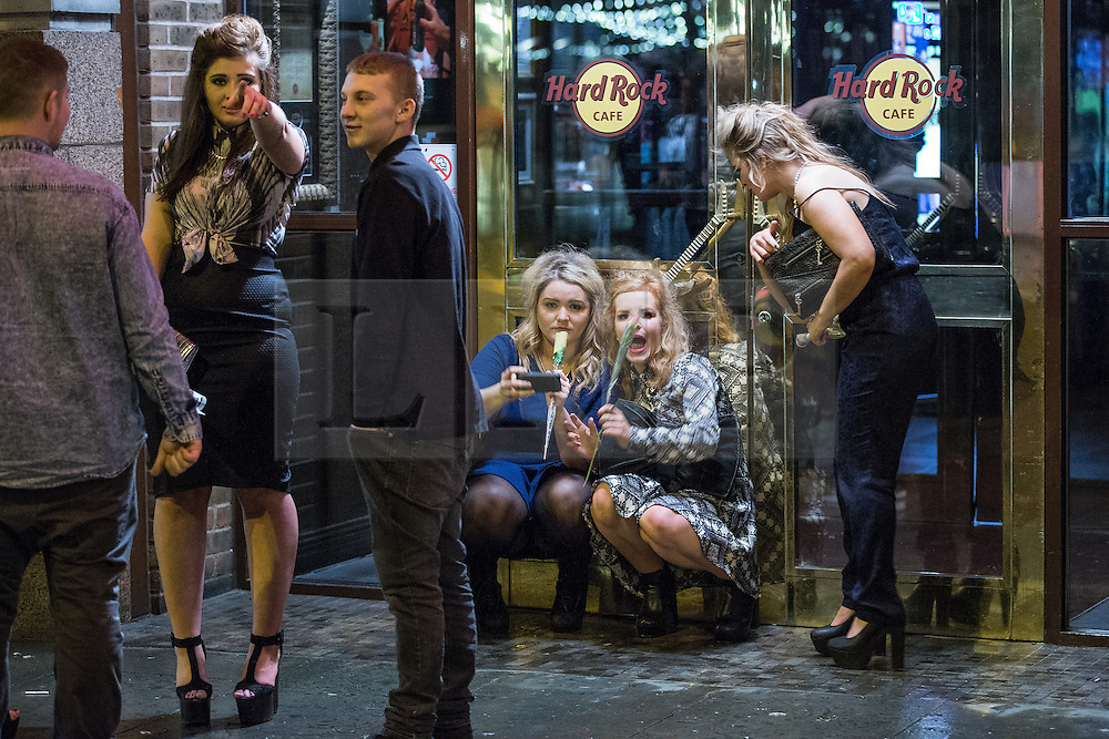 © Licensed to London News Pictures . 21/12/2013 . Manchester , UK . Women pose for a selfie in front of the Hard Rock cafe . Christmas revellers out in the rain in Manchester on Mad Friday , the last Friday night before Christmas which is typically one of the busiest nights of the year for police and ambulance crews . Photo credit : Joel Goodman/LNP