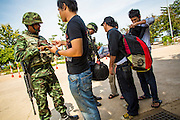 "25 OCTOBER 2012 - TAK BAI, NARATHIWAT, THAILAND: Thai soldiers check the papers of people near the Malaysian border in Tak Bai, Thailand. The ""Tak Bai Incident"" took place on Oct. 25 in Tak Bai, Narathiwat, Thailand during the Muslim insurgency in southern Thailand. On that day, a crowd gathered to protest the arrest of local residents. Police made hundreds of arrests during the protest and transported the arrested to Pattani, about two hours away, in another province. They were transported in locked trucks and more than 80 people suffocated en route. This enraged local Muslims and shocked people across Thailand. No one in the Thai army accepted responsibility for the deaths and no one was ever charged. In the past, the anniversary of the incident was marked by protests and bombings. This year it was quiet. More than 5,000 people have been killed and over 9,000 hurt in more than 11,000 incidents, or about 3.5 a day, in Thailand's three southernmost provinces and four districts of Songkhla since the insurgent violence erupted in January 2004, according to Deep South Watch, an independent research organization that monitors violence in Thailand's deep south region that borders Malaysia.   PHOTO BY JACK KURTZ"