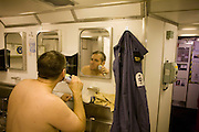 Able-bodied sailor shaves in his Junior Rating head (toilets)  aboard HMS Vigilant, a Vanguard class nuclear submarine