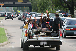 Stock photo of a group in the back of a pickup truck evacuating in preparation for Hurricane Ike