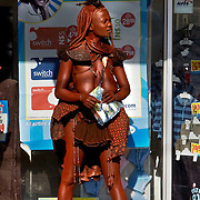 A Himba woman in traditional skins, her body covered in a mixture of fat, ash and ochre-colored mud, stands with her purchases outside of a store in the town of Opuwo in northwest Namibia. July 10, 2008. Photo by Evelyn Hockstein for The New York Times.